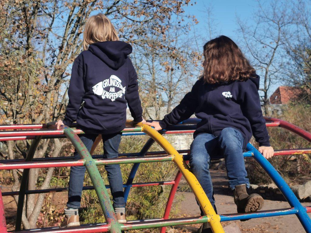 Kinder auf Klettergerüst mit Kleidung Logo Schule