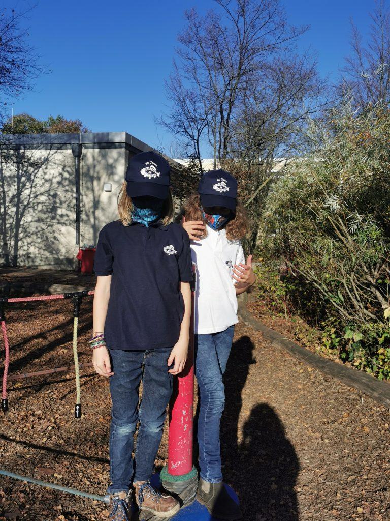 Zwei Kinder tragen Poloshirts.