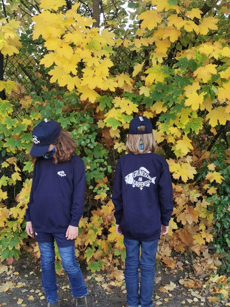 Zwei Kinder tragen Sweatshirts mit Logo.